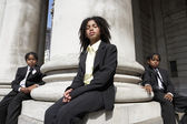 Students sitting on stone pillar — Stock Photo
