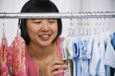 Asian woman shopping for baby clothes — Stock Photo