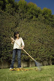 Asian woman raking leaves — Stock Photo