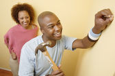 Couple hammering nail into wall — Stockfoto