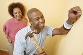 Couple hammering nail into wall — Stock Photo