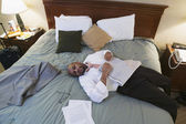 Businessman laying on hotel bed with newspaper — Stock Photo