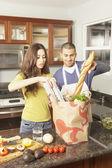 Bolsa de supermercado desembalaje joven pareja hispana — Foto de Stock