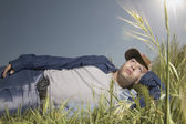 Teenage boy relaxing in grass — Stock Photo