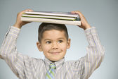Boy balancing notebooks on his head — Stock Photo