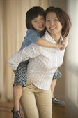 Asian mother giving young daughter piggyback ride indoors — Stock Photo