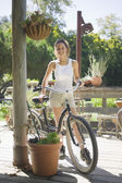 Woman with bicycle outdoors — Stock Photo