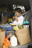 Boy sitting in backseat of car eating with groceries — Stock Photo