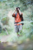 Man using binoculars while hiking — Stock Photo