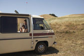 Family looking out of recreational vehicle window — Stock Photo