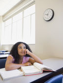 African girl day dreaming at desk in classroom — Stock Photo