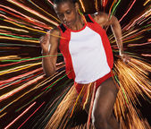 Female athlete running through threads of color — Stock Photo