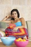 Jeune femme assise sur le canapé — Photo