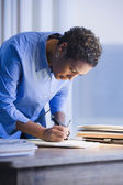 African businesswoman writing on paperwork — Stock Photo
