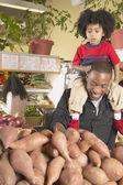 Süpermarkette omuzlarında genç oğlu ile afrikalı-amerikalı babası — Stok fotoğraf