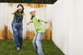 Mother and daughter painting fence — Stock Photo