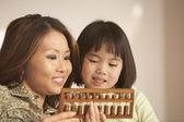 Madre e hija utilizando un ábaco juntos — Foto de Stock