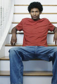 Portrait of a young man sitting on steps in a house — Stock Photo