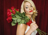 Young woman carrying a bouquet of roses over her shoulder — Stock Photo
