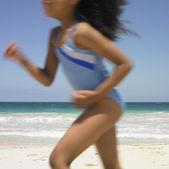 Blurred image of girl running on beach — Stock Photo