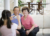 Asian girl taking photograph of grandparents — Stock Photo