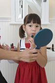 Young girl applying lipstick — Stock Photo