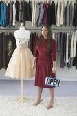 Kobieta pracowników posiadających znak otwarty w sklepie odzieżowym — Zdjęcie stockowe
