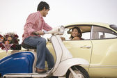 Man on scooter talking to woman in car — Stock Photo