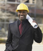 African American businessman holding blueprints — Stock Photo