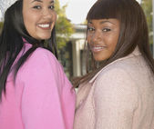 Two African American women looking over shoulders smiling — Stock Photo