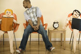 African man sitting in waiting area next to blowup dolls — Stock Photo