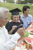 Older graduate celebrating with family — Stock Photo
