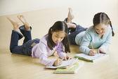 床に宿題をやっている 2 人の女の子 — ストック写真