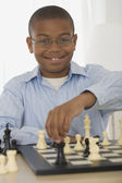 African boy playing chess — Stock Photo