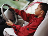 African boy pretending to drive car — Stock Photo