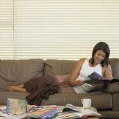 Asian woman reading magazine on sofa — Stock Photo
