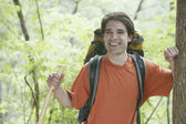 Young man backpacking in forest — Stock Photo