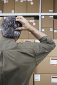 Businessman in warehouse scratching his head — Stock Photo