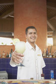 Hispanic male bartender offering up a pina colada — Stock Photo