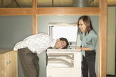 Businesswoman photocopying colleague's head — Foto Stock