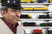 Man with conductors hat in hobby shop — Stock Photo