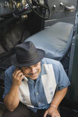 Middle-aged Hispanic man talking on cell phone in classic car — Stock Photo