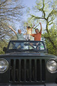 Grandparents and grandson standing in jeep with arms raised — Stock Photo