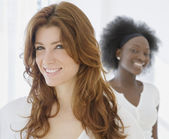 Woman smiling with African friend in background — Stock Photo