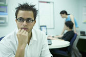 Young man sitting in an office with working behind — Stock Photo