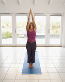 Full view of woman stretching with arms above head — Stock Photo