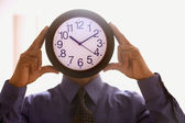 Businessman holding a clock before his face — Stock Photo