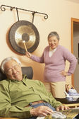 Senior Asian woman waking up senior Asian man with gong — Stock Photo
