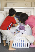 Brother and sister putting laundry in dryer — 图库照片