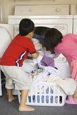 Bruder und schwester, die wäsche im trockner setzen — Stockfoto